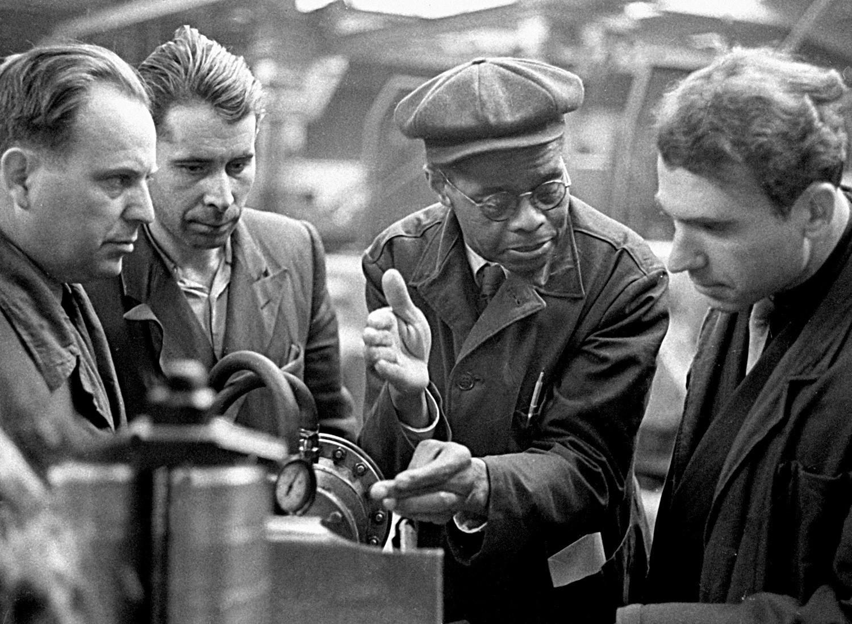 Inženir Robert Robinson [drugi z desne] v Prvi državni tovarni ležajev daje navodila delavcem.