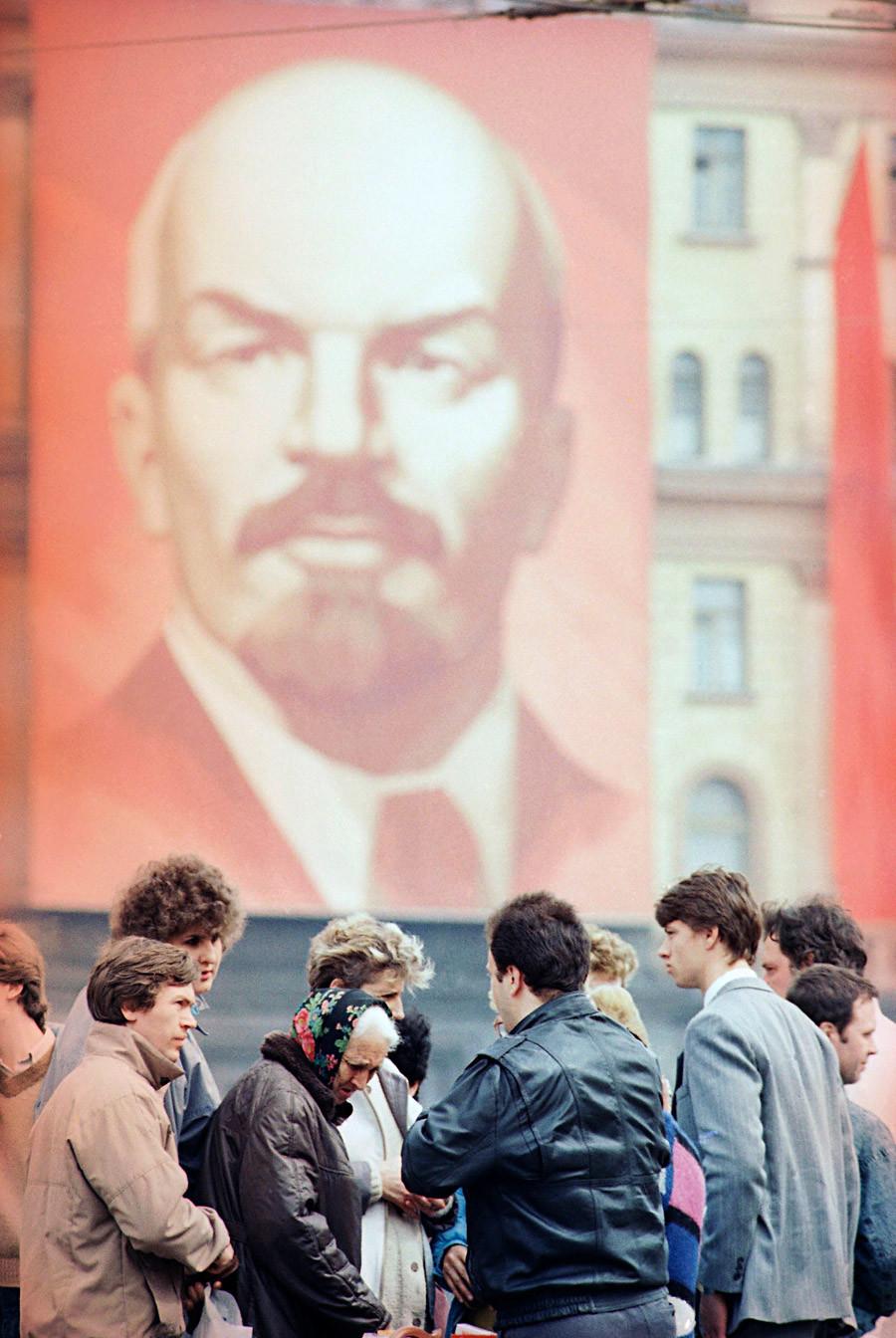 """Совјетски купци игноришу џиновски Лењинов портрет док """"на црно"""" купују америчке жвакаће гуме у Москви. Уторак, 30. април 1991, уочи првомајских празника."""