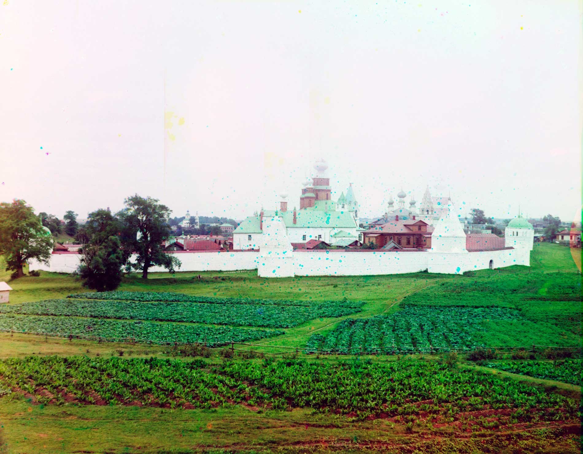 Intercession Convent, north view. Center: Church of St. Anne & ​Intercession Cathedral with three domes. Right: Church of Sts. Peter&Paul (beyond convent). Foreground: potato plots. Summer 1912