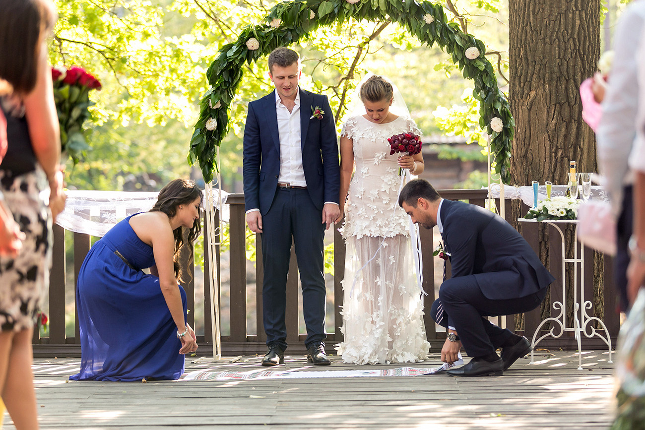 Pasangan yang baru menikah menjalankan ritus kesatuan tradisional selama upacara pernikahan.