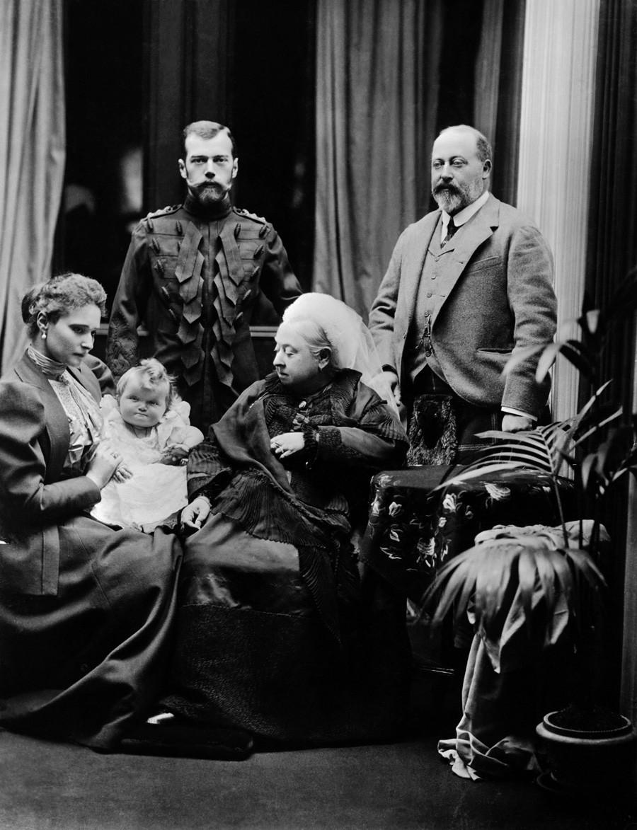 Ruska carica Aleksandra Fjodorovna (v rokah drži kneginjo Olgo), Nikolaj II. v uniformi Kraljevskega polka škotskih dragoncev, britanska kraljica Viktorija in vojvoda Velški Albert Edward. Grad Balmoral, Škotska, 1896.