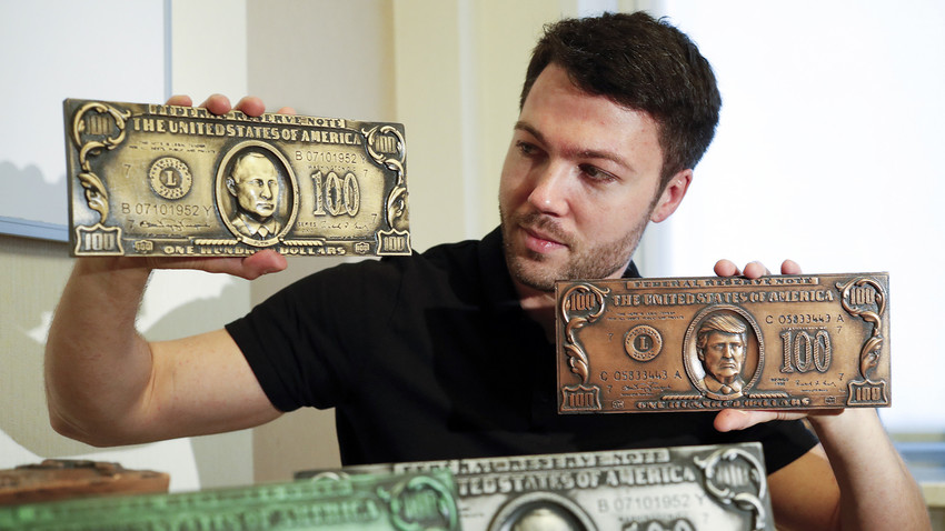Former hacker Sergey Pavlovich holds mock money printing plates with Russian President Putin, left, and U.S. President Donald Trump faces in place of Benjamin Franklin during an interview with the Associated Press in Moscow, Russia, Wednesday, Aug. 9, 2017