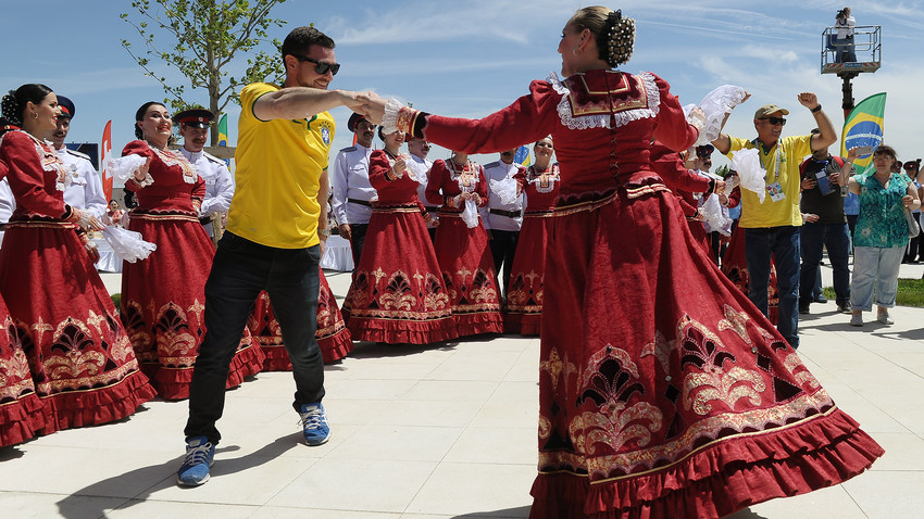 Brazil's fan dance with a woman in traditional dress upon arrival in Rostov-on-Don, Russia, on June 17, 2018. All fans were presented with Cossack caps.