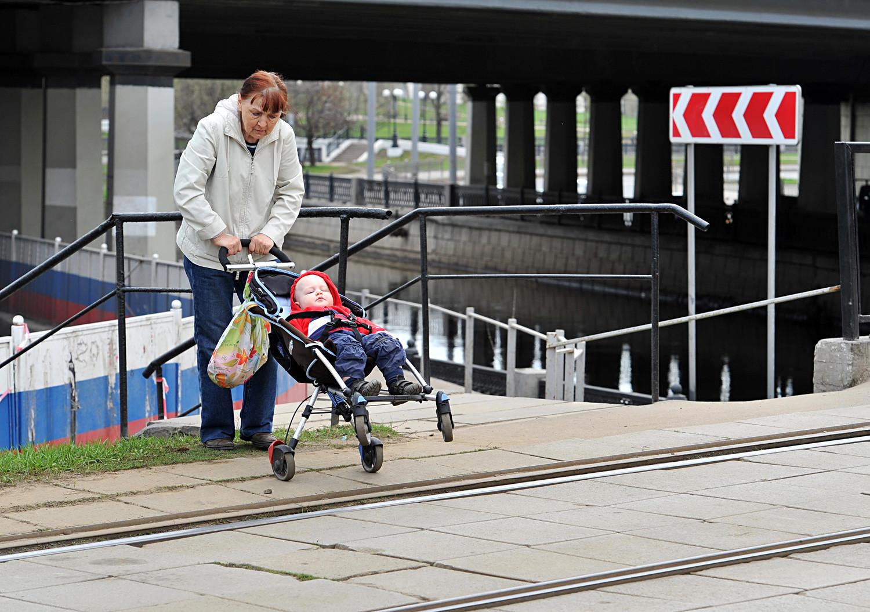 Seorang perempuan dan bayinya menyeberang jalan.