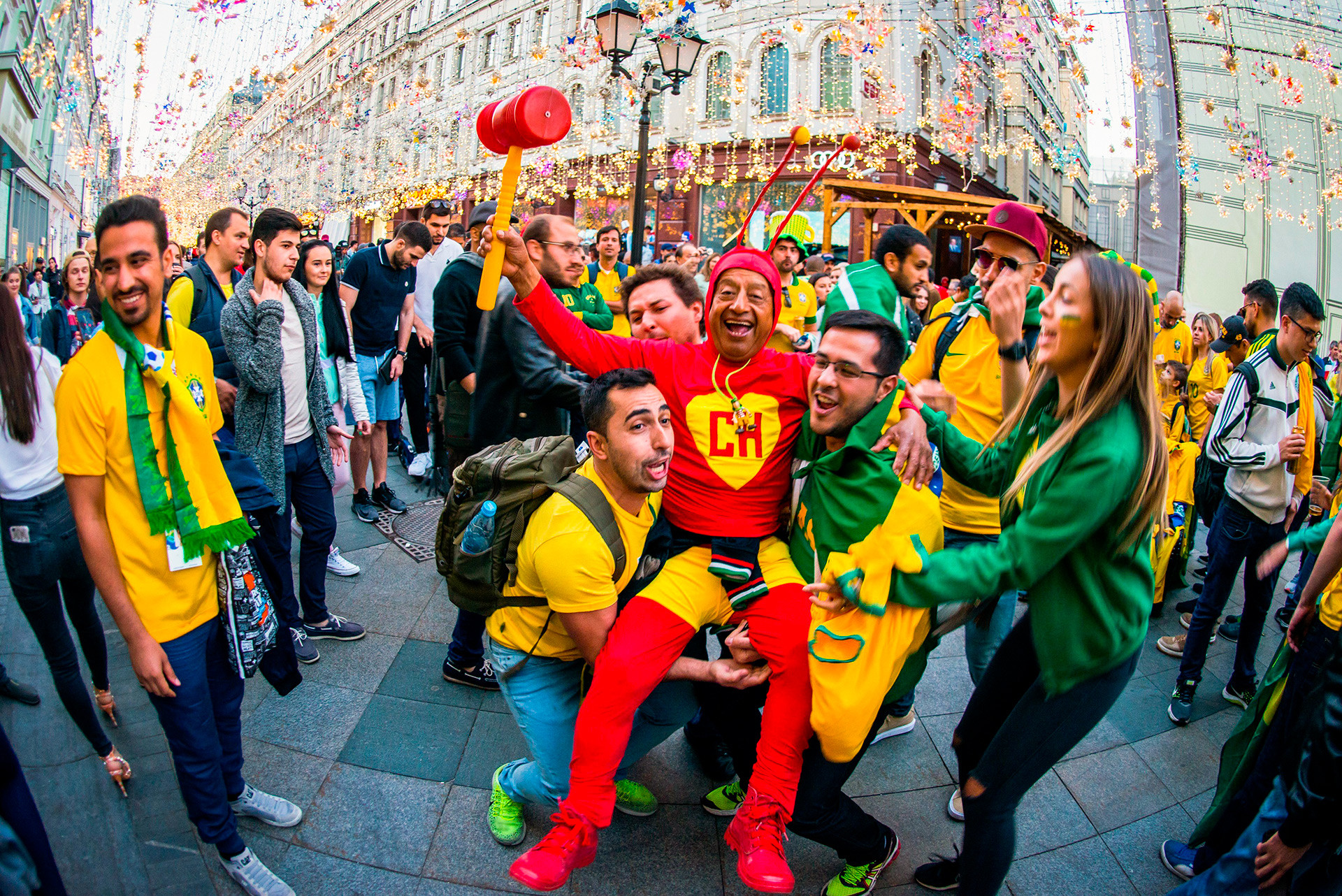 Brazil fans give a leg up to a Swiss supporter dressed as an insect – because why not!