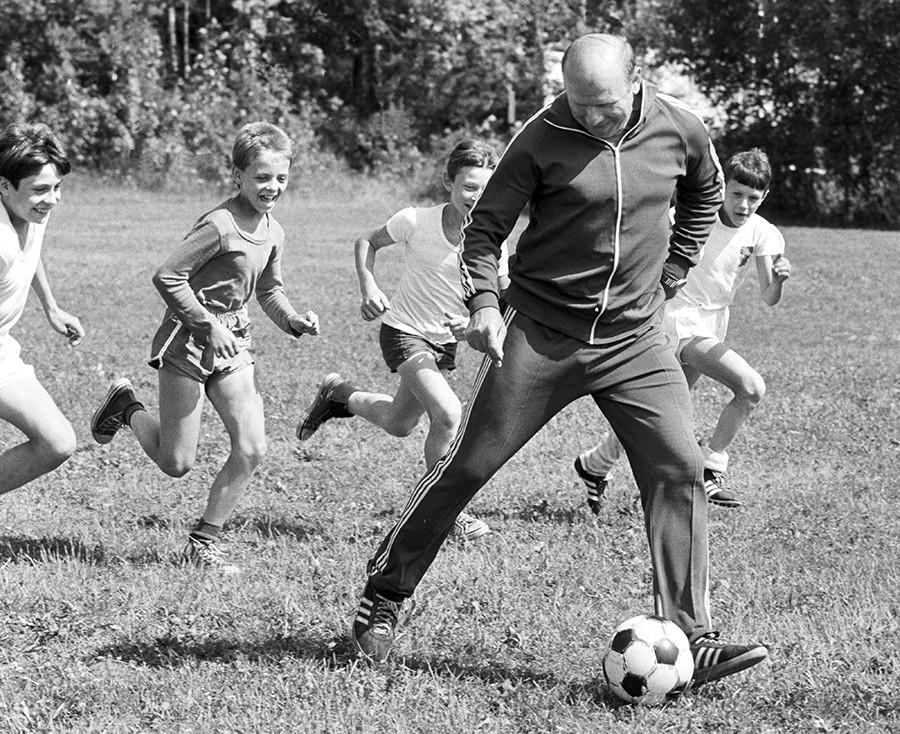 """Ветеран совјетског фудбала Едуард Стрељцов (у предњем плану) игра фудбал са децом у летњем спортском кампу """"Млади торпедиста""""."""