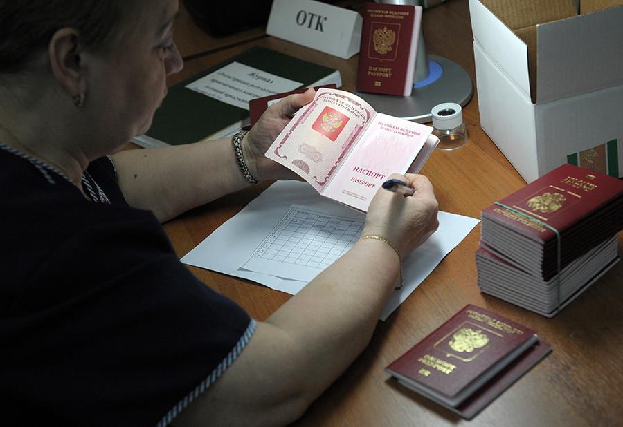 Une employée de l'Entreprise fédérale unitaire d'État Goznak contrôle la qualité des passeports biométriques tout juste réalisés et destinés à des citoyens russes, au sein du Centre de personnalisation de Goznak, à Moscou.