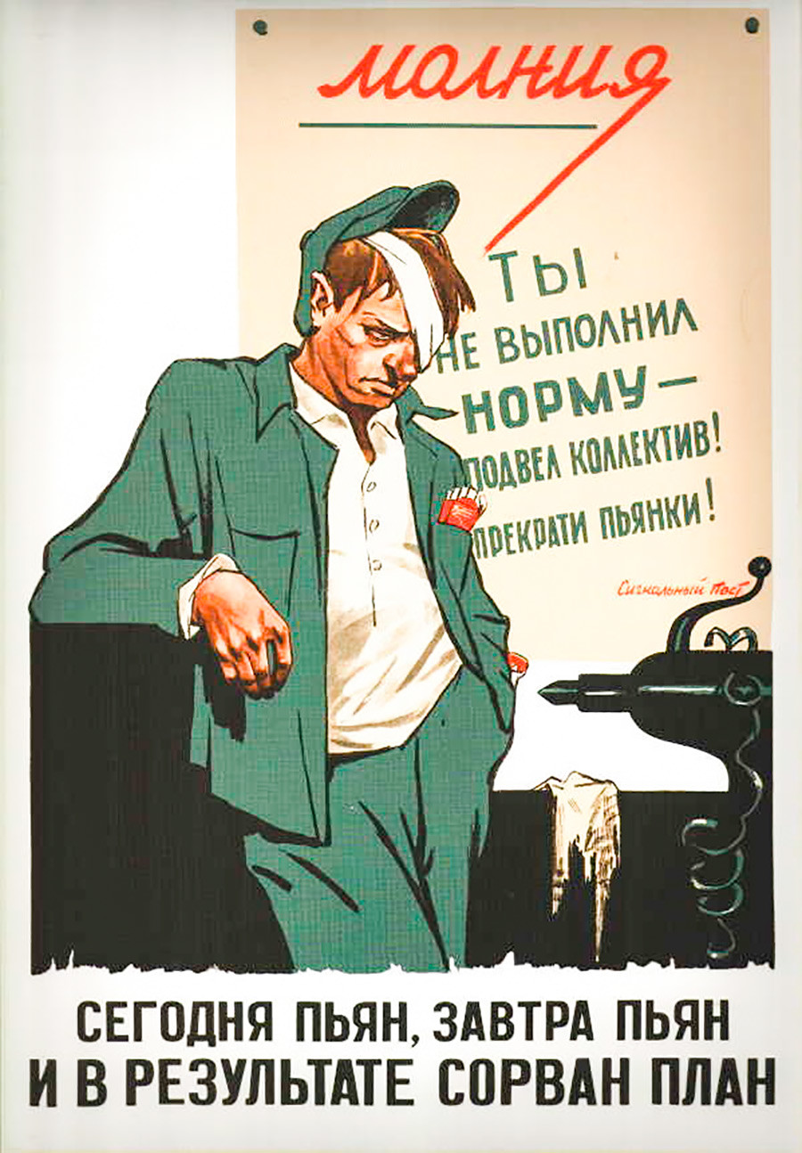 The poster behind his back says: 'You didn't fulfill the work norms – you've failed the team! Stop binges!' The inscription below says: 'Drunk today, drunk tomorrow – work plan is disrupted!'