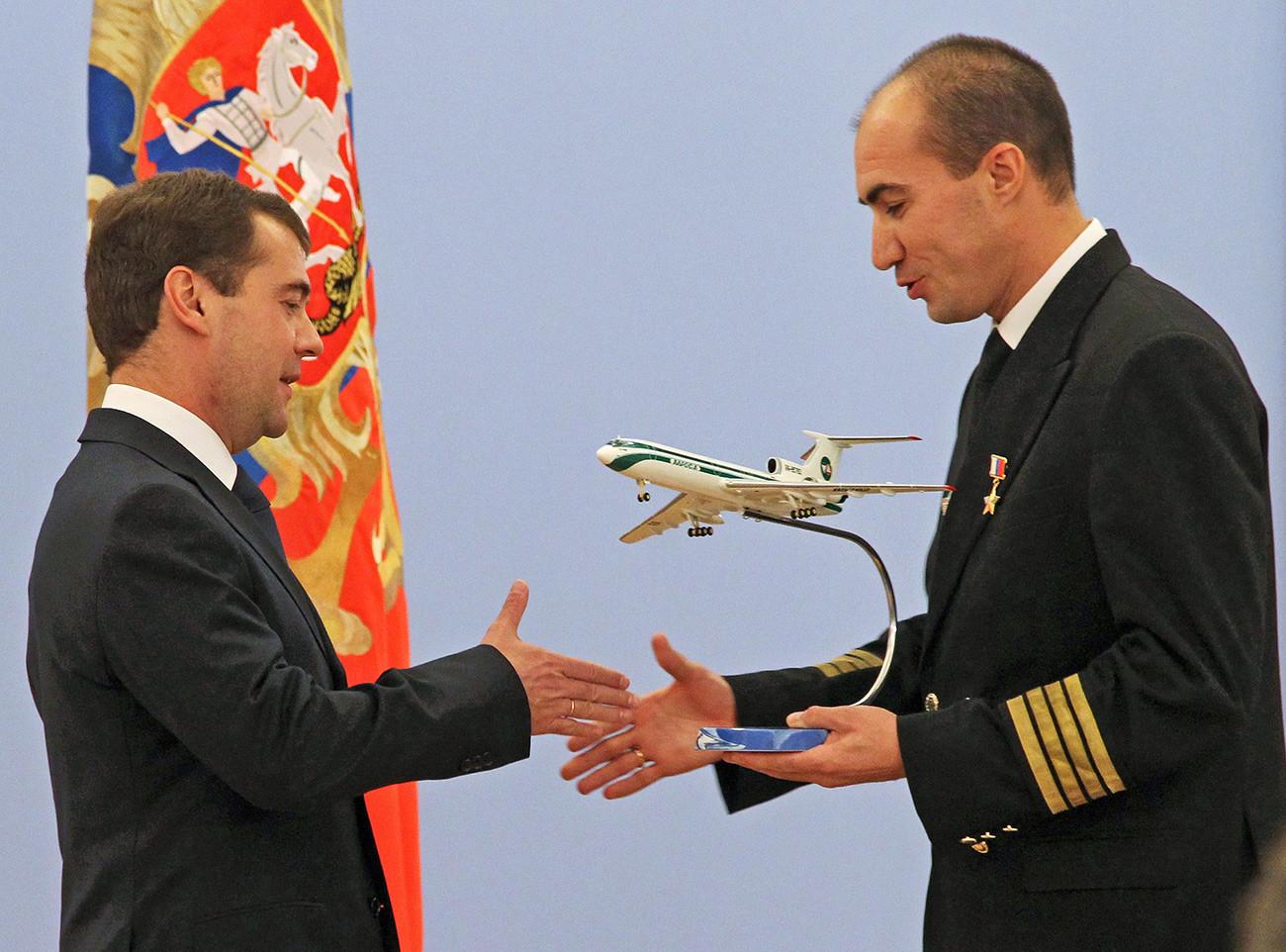 O então presidente russo Dmítri Medvédev parabeniza o capitçao do Tu-154, Evguêni Novoselov, que recebeu o título de Herói da Rússia.