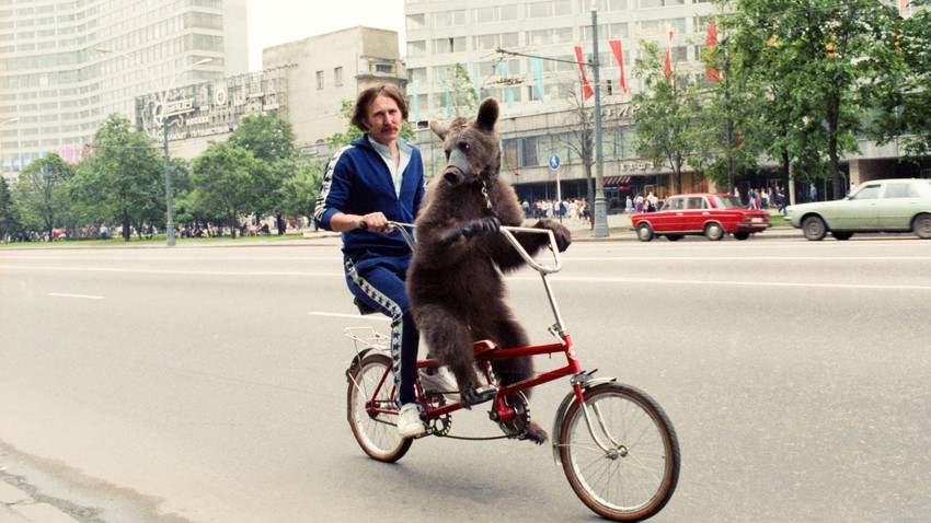 Nikolai Zobov, que trabalha no circo, passeando com seu urso em Moscou em 22 de junho de 1969.