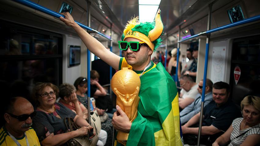 Seorang penggemar dengan bendera Brasil melakukan perjalanan di kereta bawah tanah ke Stadion Spartak.