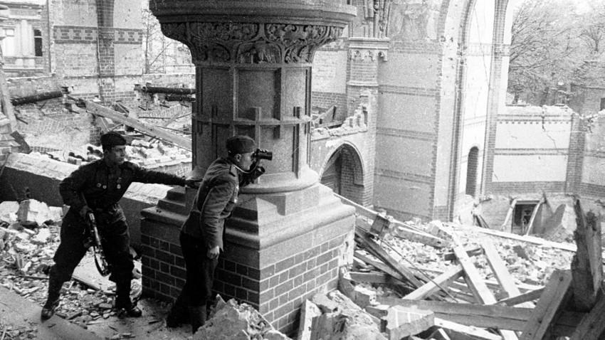 Seorang perwira Soviet mengeker tembakan artileri di Berlin yang hancur, 30 April 1945.