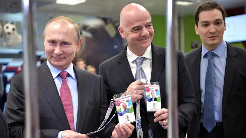 Presiden Rusia Vladimir Putin (kiri) and Presiden FIFA Gianni Infantino (tengah) mengunjungi pusat pendistribusian 'Fan ID' di Sochi, Rusia.