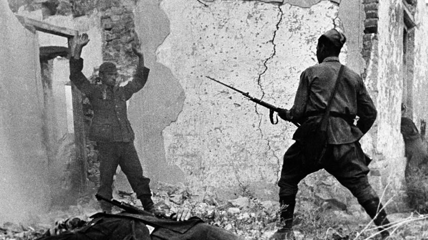 Seorang pria Soviet bersenjata menahan seorang tentara Nazi dekat Mozdok, Ossetia Utara, pada September 1942.
