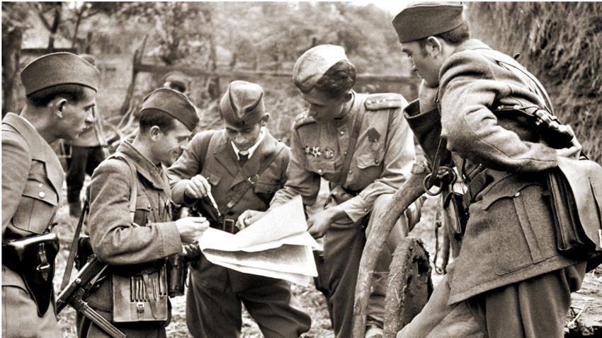 Štab brigade jugoslovanskih partizanov in oficir Rdeče armade sprejemajo odločitev pred bojem, oktober 1944.