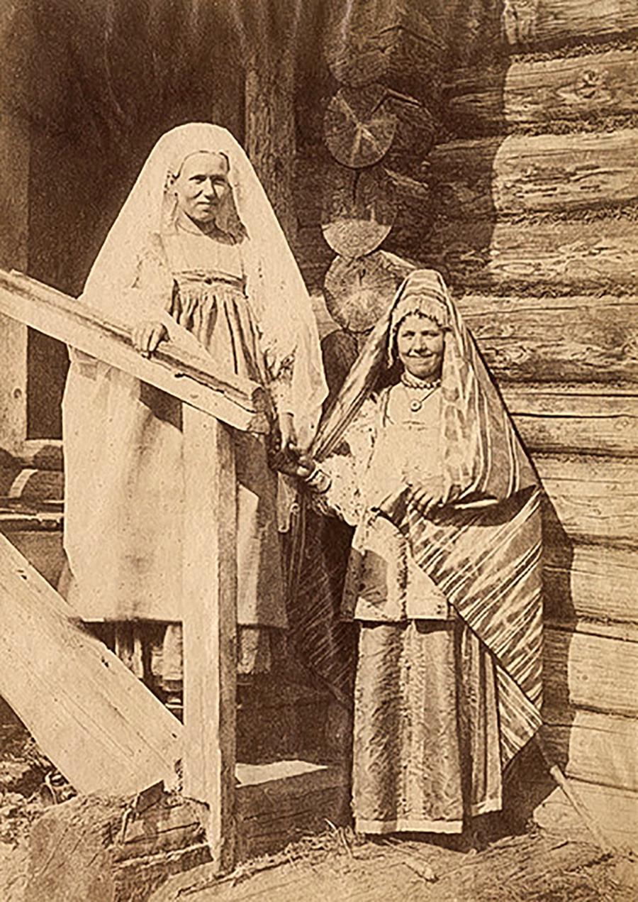 Seorang perempuan dan wanita bersuami dalam kostum perayaan.