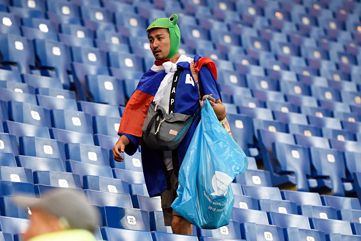 Seorang suporter Jepang mengumpulkan sampah setelah pertandingan sepak bola Piala Dunia 2018 antara Belgia dan Jepang di Rostov Arena di Rostov-On-Don, pada 2 Juli 2018.