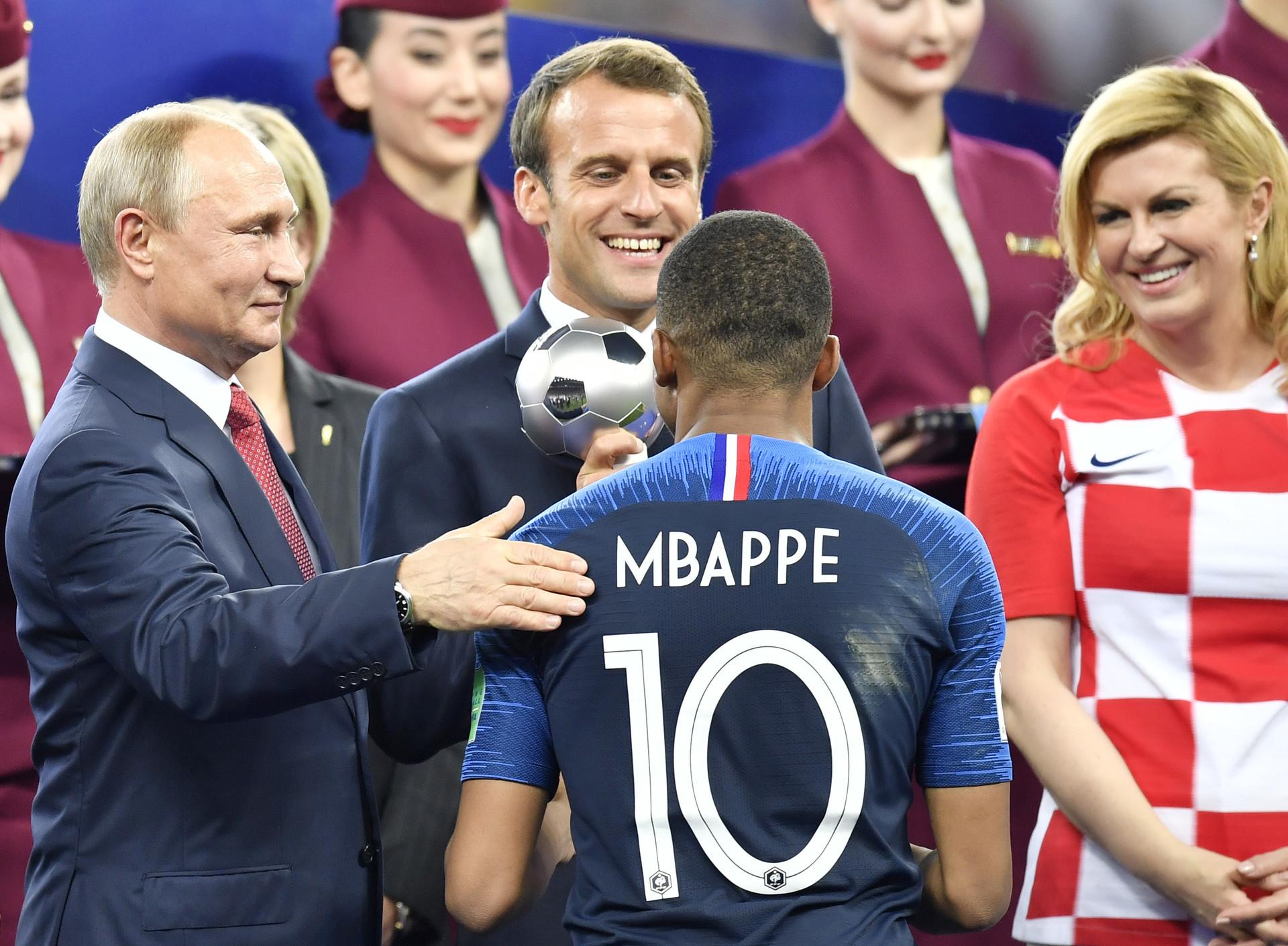 Dari kiri ke kanan: Presiden Rusia Vladimir Putin, Presiden Prancis Emmanuel Macron, dan Presiden Kroasia Kolinda Grabar-Kitarovic memberikan penghargaan kepada pemain Prancis Kylian Mbappe sebagai pemain muda terbaik setelah Prancis memenangkan Piala Dunia, Minggu (15/7).