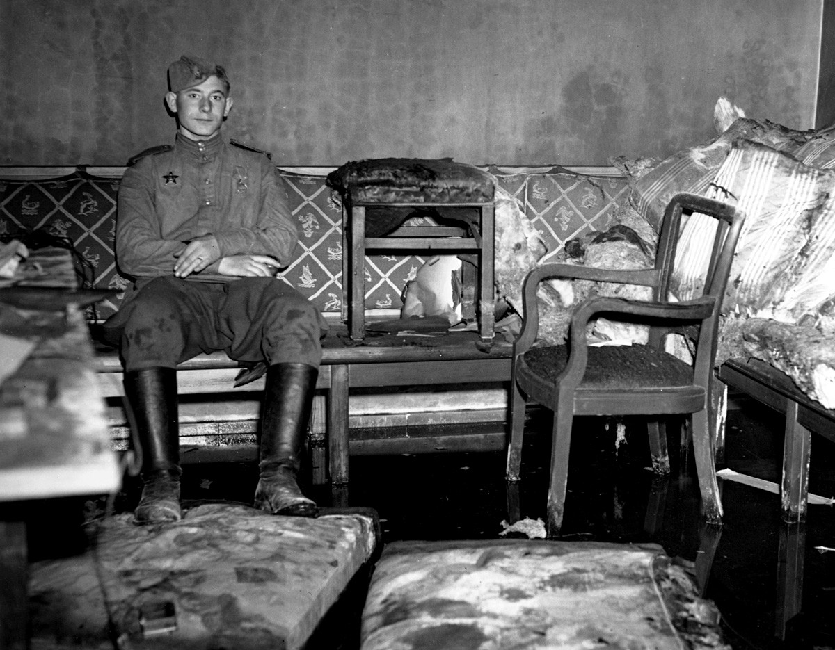 A Russian soldier sitting on the sofa upon which German dictator Adolf Hitler is reported to have killed himself,
