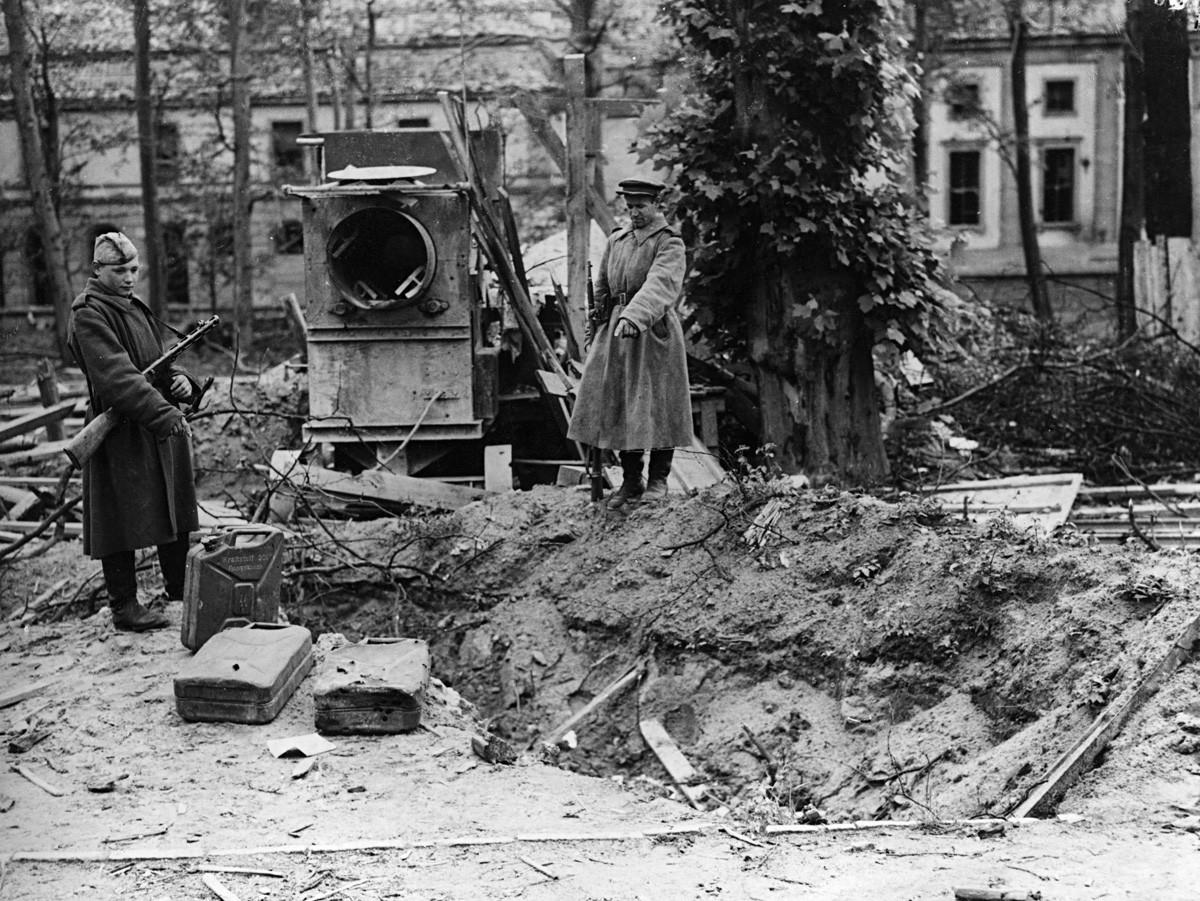 Dua tentara Soviet menunjukkan apa yang diduga sebagai kuburan Hitler di belakang Reichskanzler di Berlin.