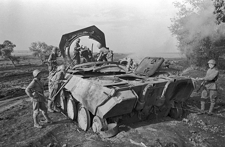 Soviet soldiers standing by a Nazi self-propelled gun Panther destroyed by the Soviet artillery in Prokhorovka. The Kursk Bulge.
