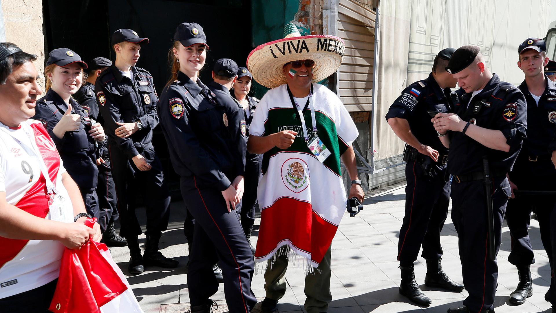 Pendukung tim nasional Meksiko dan Peru dengan polisi Rusia di Moskow, Rusia, 15 Juni 2018.