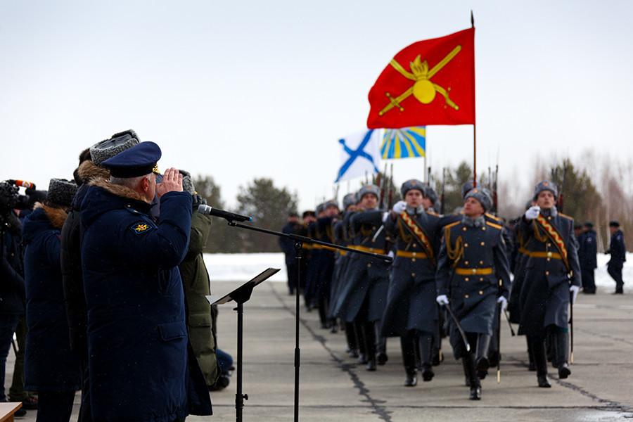 Војниците со знамето на ВКС го пречекаа претседателот Путин кога во декември ја посети базата Хмејмим и го прогласи крајот на руската операција во Сирија