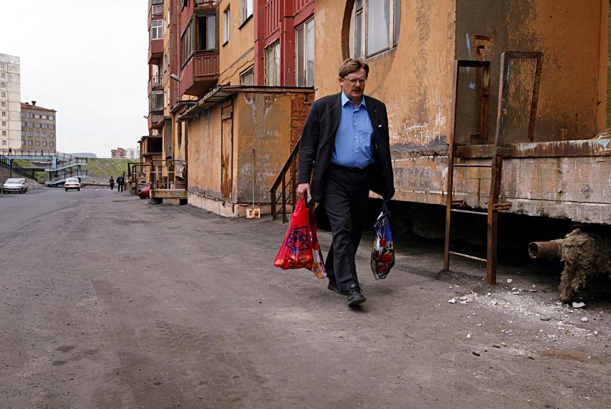 ロシアのノリリスクで農産物のマーケットから戻っている男性。この北部の街の永久凍土では植物を育てることができないので、全ての食料品が輸入されている。