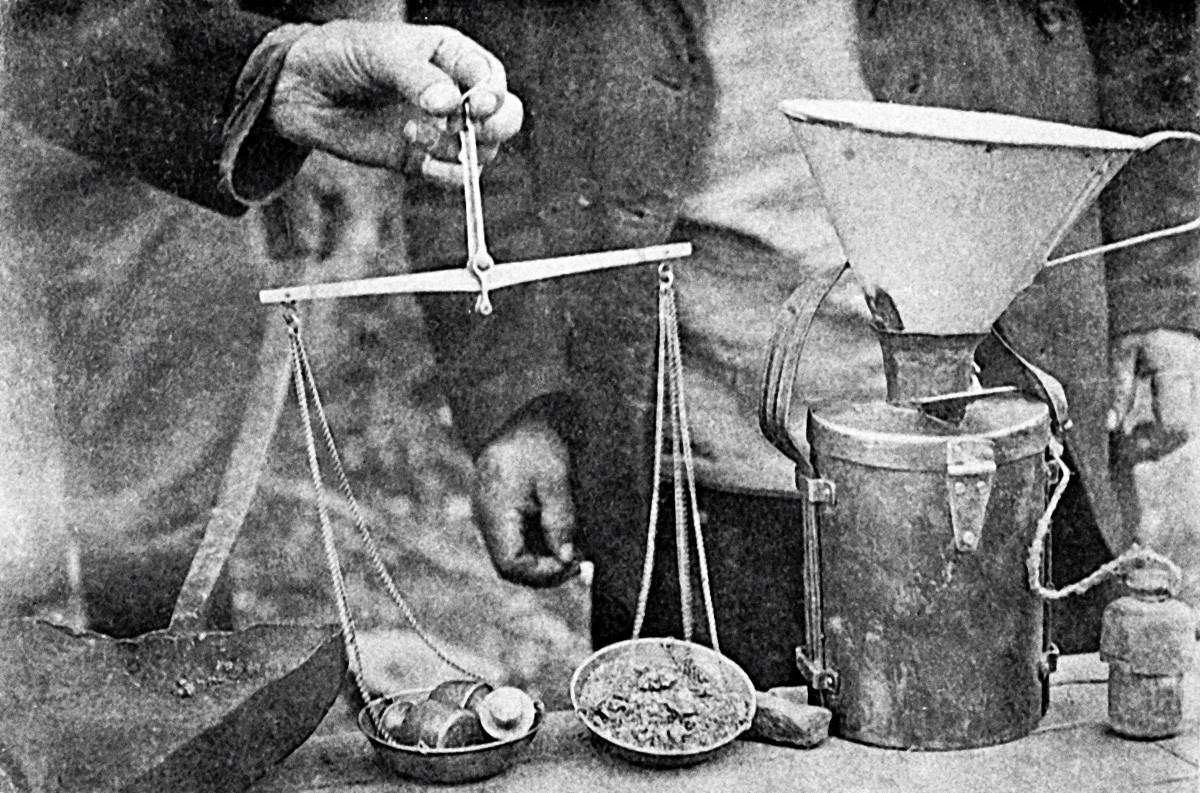Recebimento e pesagem de ouro no escritório nas minas. Região de Irkutsk, 1909