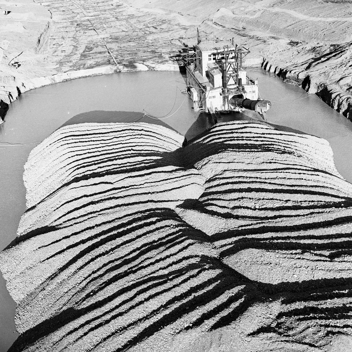 A dredge in the Aliskerov Gold Field near the city of Bilibino on the Kolyma River, Magadan Region, having a processing capacity of several thousand tons of gold dust per day and replacing hundreds of workers. 1964. - -