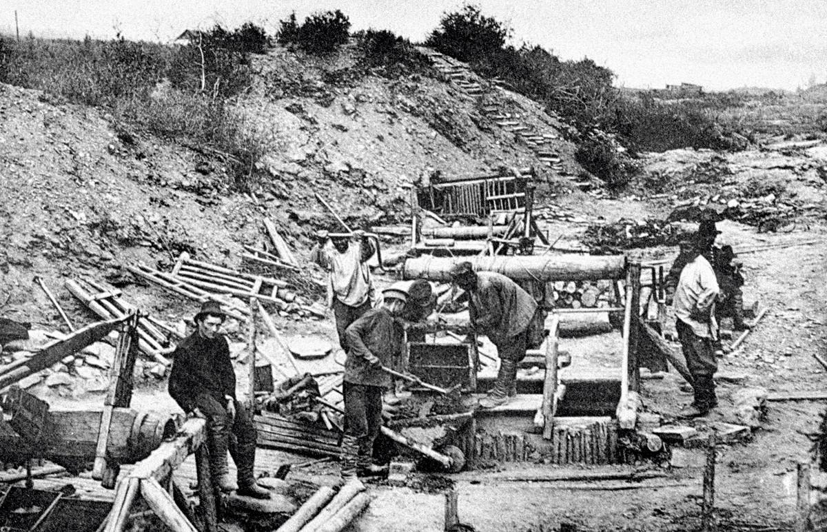 ミハイロー・アルハンゲルスキー金山での「スタラーテリ」(試掘者)という採金の会社による金を含んでいる鉱石が手で採掘されている。 イルクツク州、ロシア帝国、1908年。
