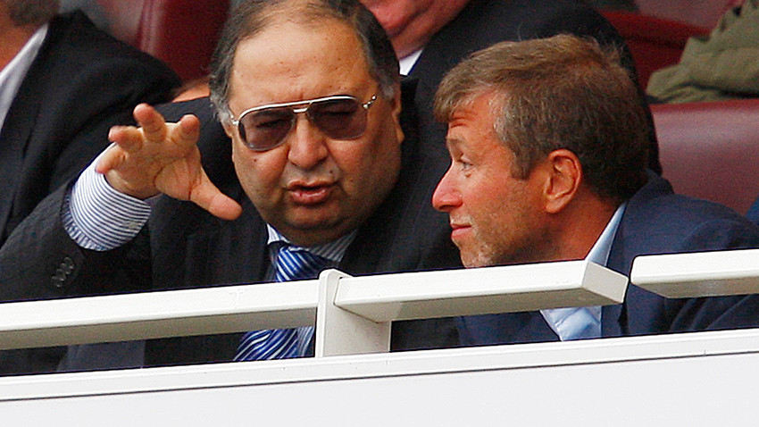 Alisher Usmanov (L) talks to Roman Abramovich after the English Premier League match between Arsenal and Chelsea in London