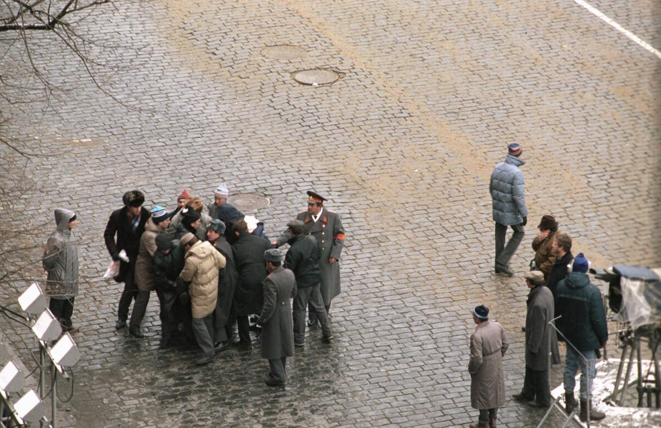 Policial e transeuntes detêm Chmonov na Praça Vermelha após ele dar dois tiros em direção a Gorbatchov na celebração da Revolução de Outubro.