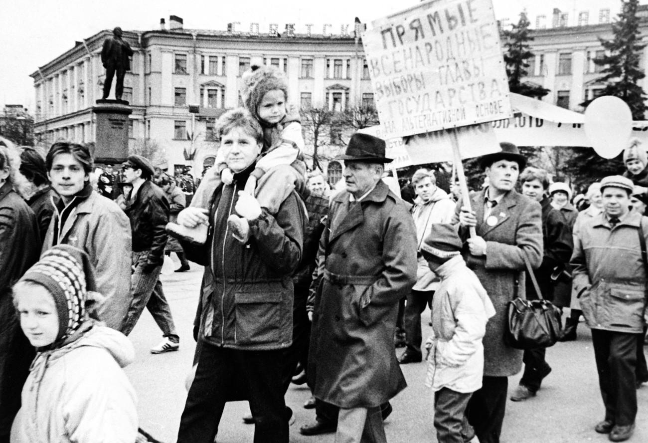 Esta foto mostra Aleksandr Chmonov (carregando um cartaz) no primeiro semestre de 1990, durante campanha eleitoral no subúrbio de Kolpino, em Leningrado.