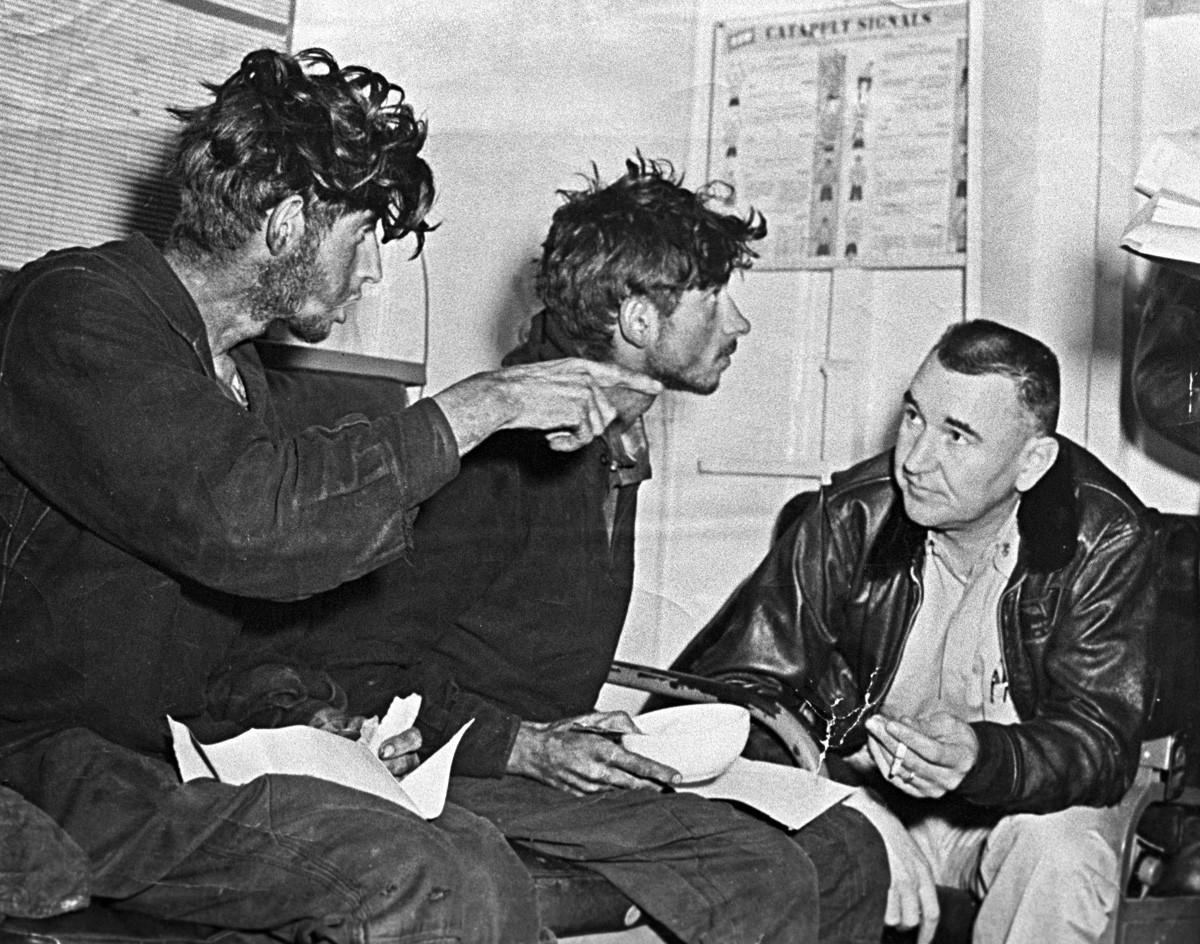 異常なほどやせ衰えたアスハト・ジガンシンとフィリップ・ポプラフスキーがアメリカの船員に状況を伝えている」。1960年。