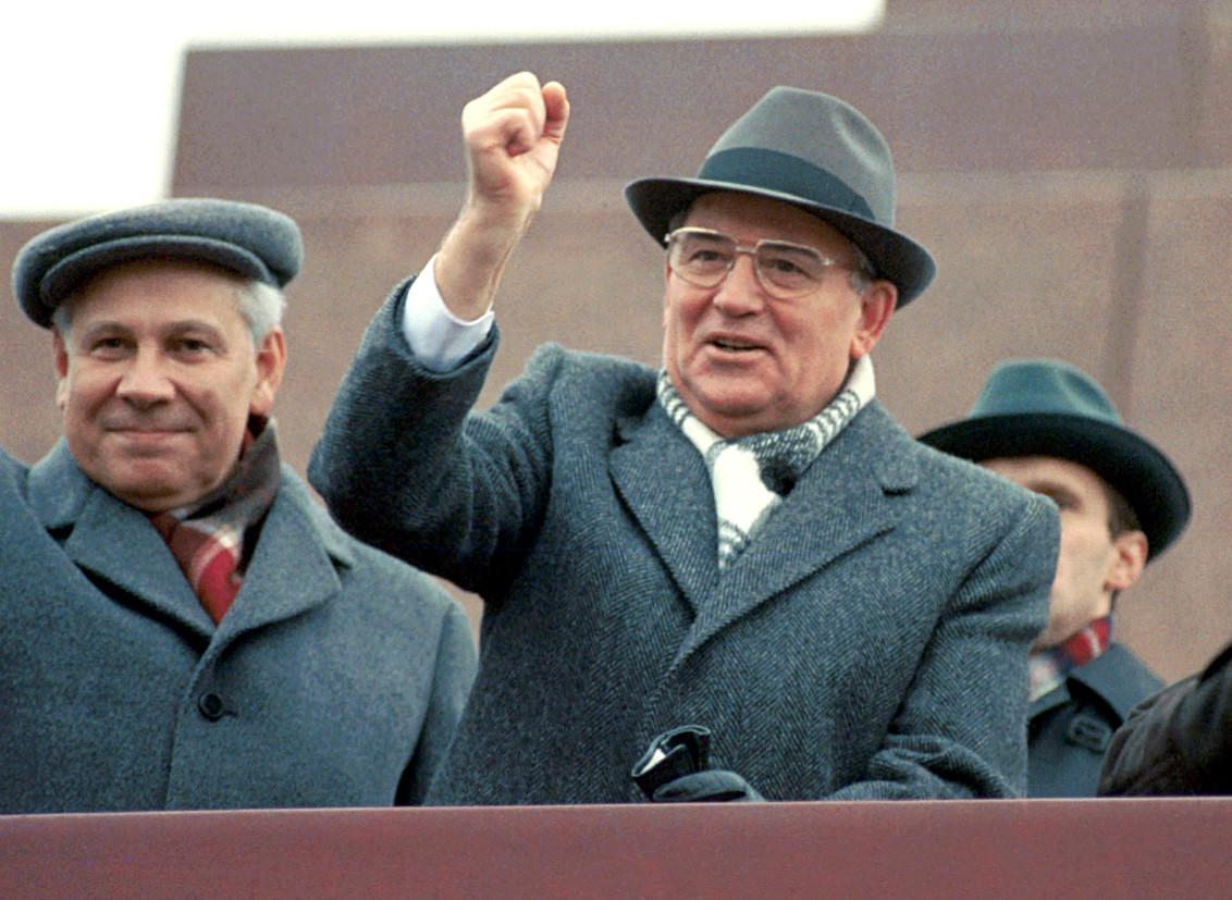 モスクワ、ソ連。ソビエト連邦共産党書記長、ミハイル・ゴルバチェフ(右)が十月革命の73年の記念日を祝う軍事パレードで身ぶりをしている。彼は赤の広場のレーニン廟の講壇に立っている。1917 年11 月7 日。