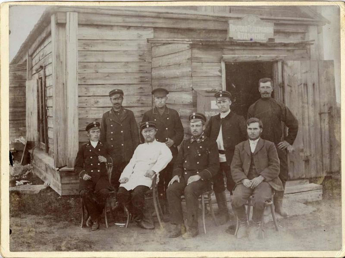 Carteros posan delante de una oficina de correos, década de 1900.