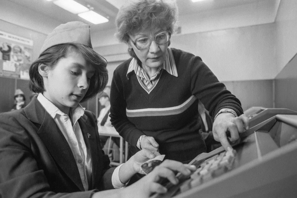 Empleada instruye a una compañera que se acaba de incorporar, 1987.