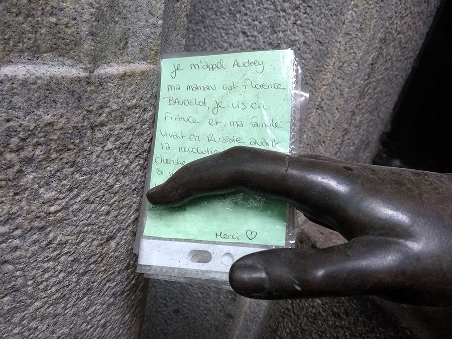 The note in the statue's hand.