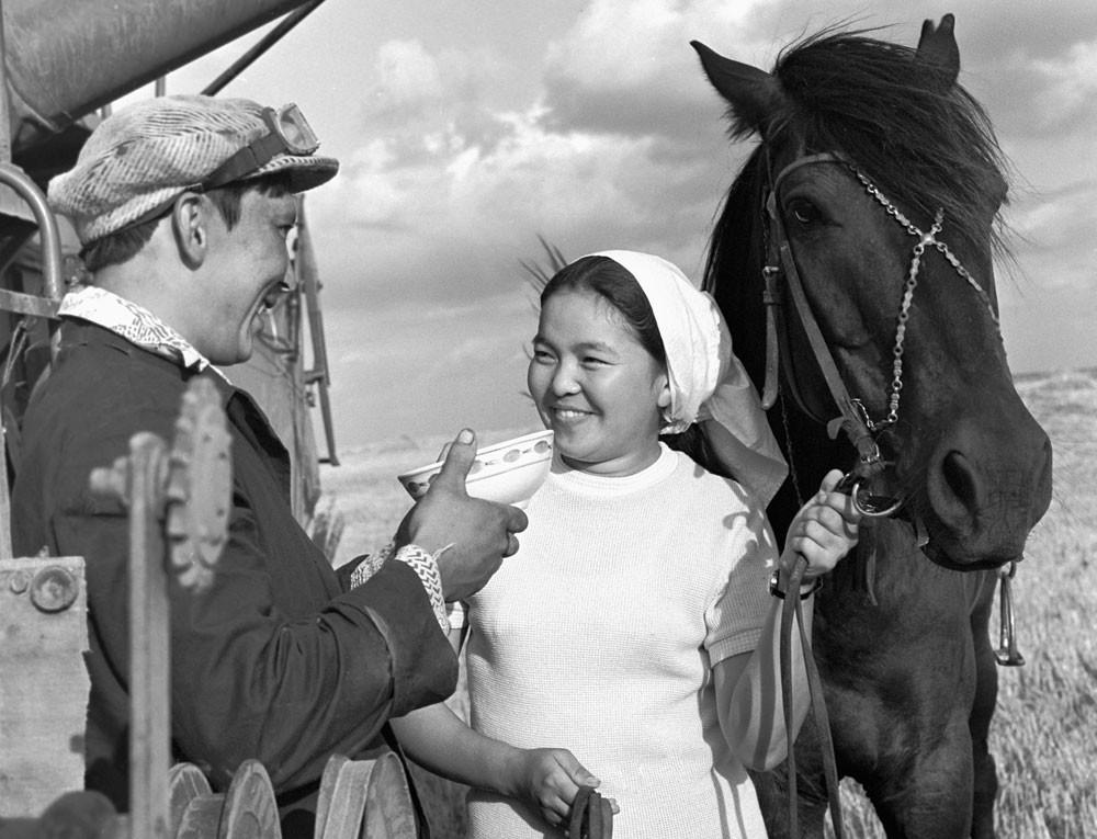1976. Ordenhadora do Cazaquistão oferece tigela de kumis a um motorista de colheitadeira