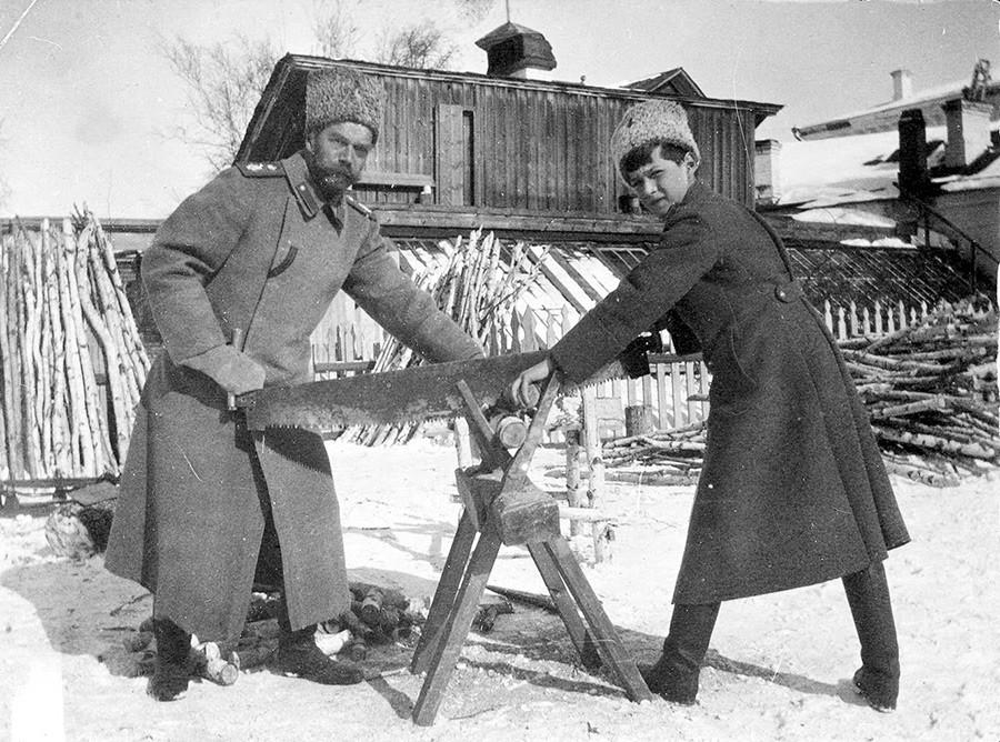 O tsarêvitch Aleksêi e o tsar Nikolai 2° serrando madeira em Tobolsk, em 1917 .