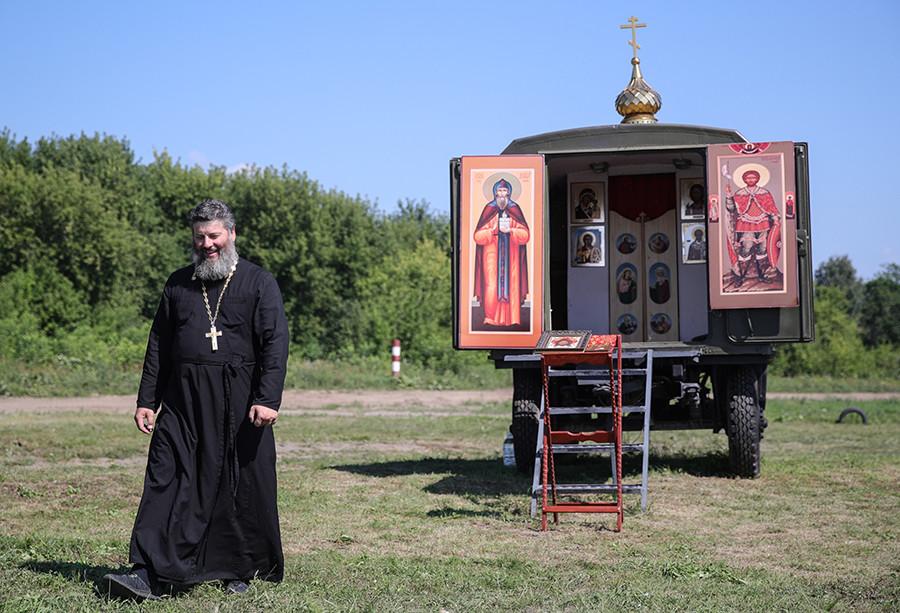 Padre ortodoxo diante de capela móvel.