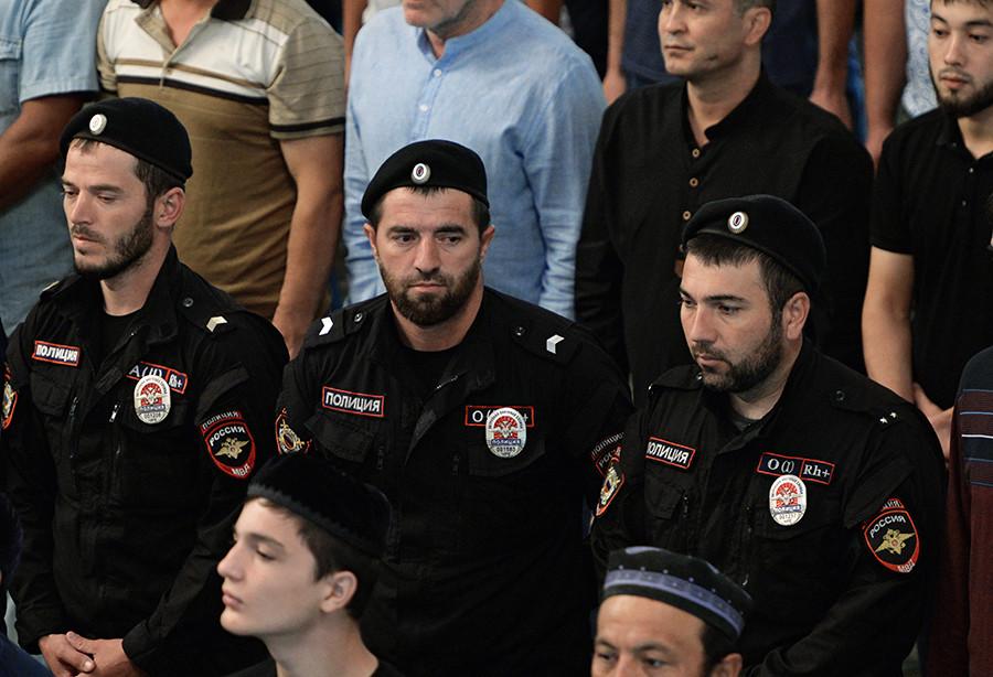 Tiga orang polisi tampak berada di antara jemaah yang hendak melaksanakan salat Id di Masjid Jantung Chechnya, Grozny, Republik Chechnya, Rusia.