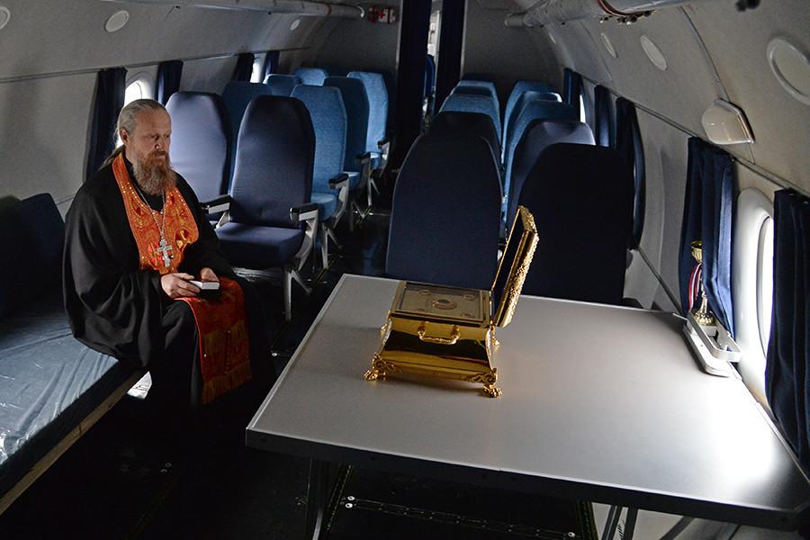 Митрополит Никодим от Челябинск и Златоуст по време на служба пред иконата на Св. Георги и неговите свети мощи на борда на самолета.