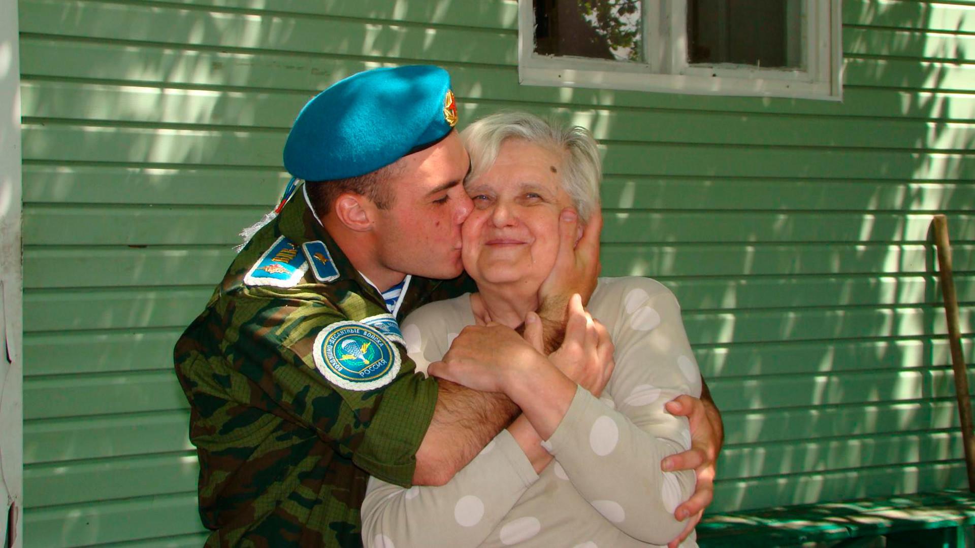 Filho adotivo enche Tatiana de beijos antes de partir para servir ao exército, em maio de 2018.