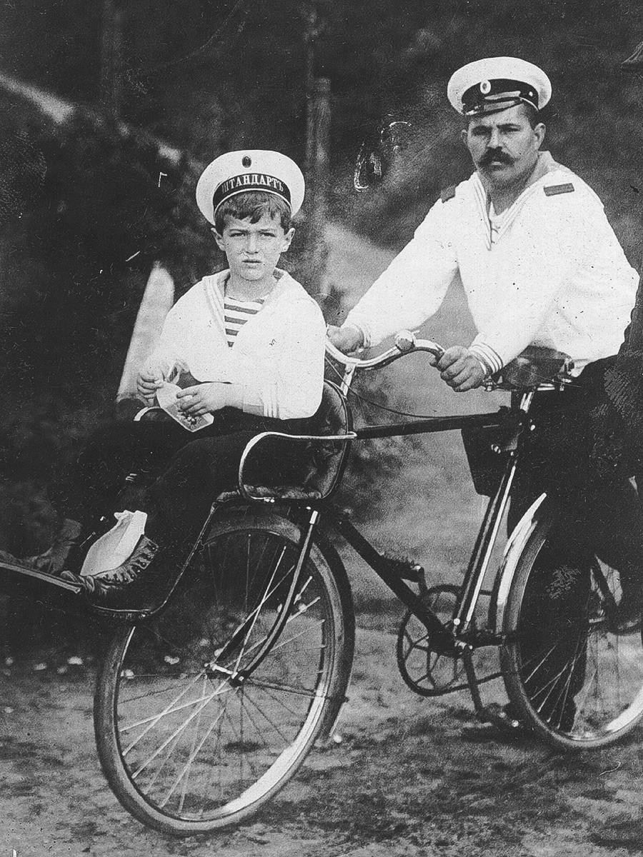 Občasno je z Aleksejem bilo tako hudo, da ni mogel hoditi. Na kolesu mu dela družbo njegov »morski varuh«; Friedberg, Hesse, 1910.