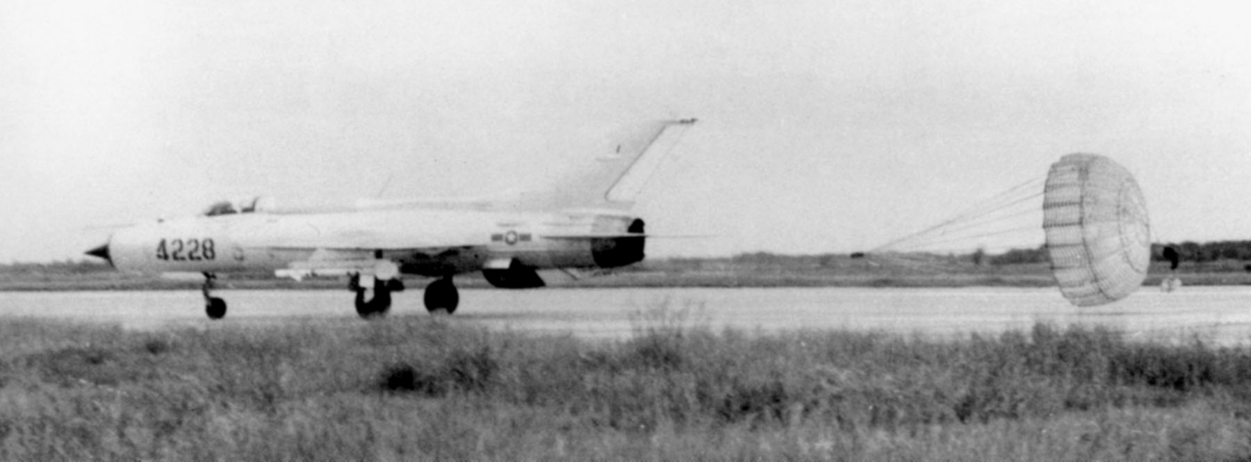 MiG-21 PF de la Fuerza aérea norvietnamita despliega su paracaídas de frenada al aterrizar tras realizar una misión. El avión está armado con misiles aire-aire AA-2 Atoll.
