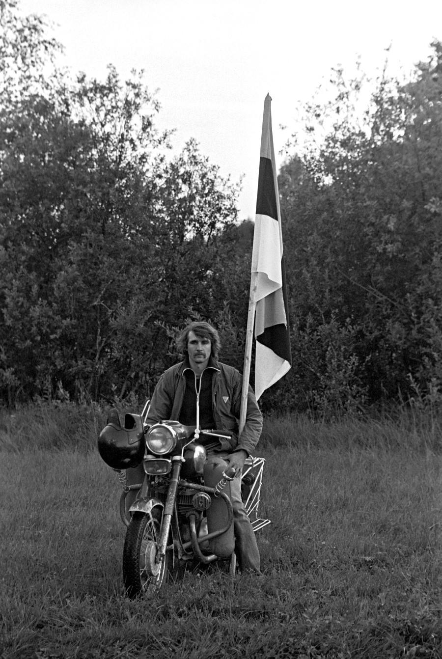 Homem ergue a bandeira nacional da Estônia na