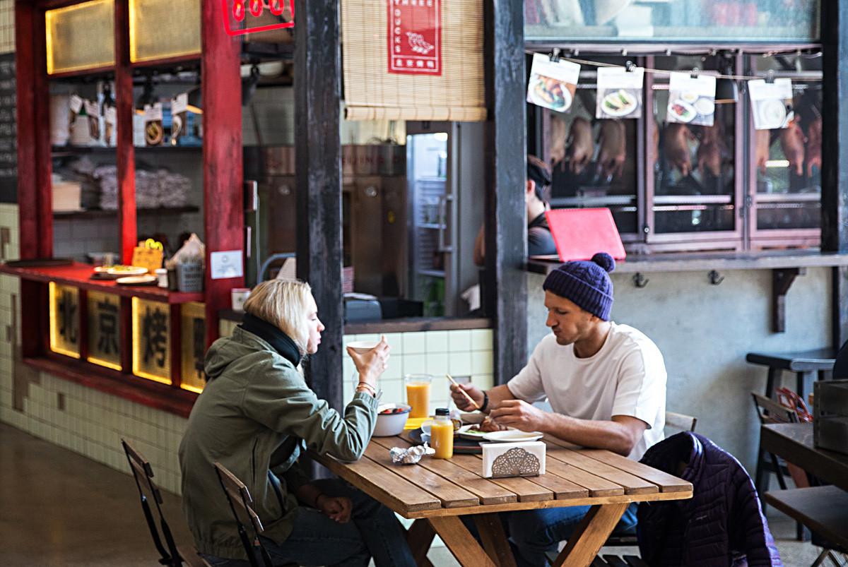 Пара обедает в кафе на Даниловском рынке в Москве.