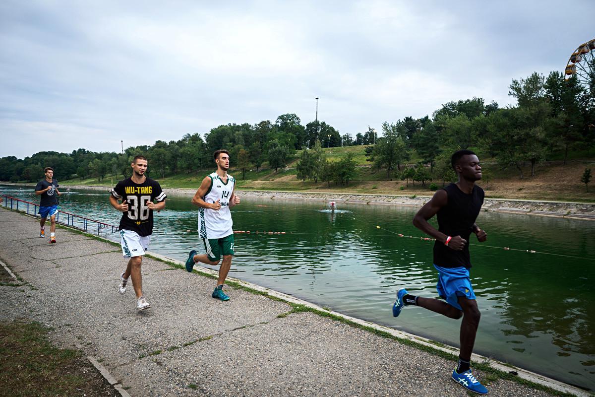 Молодые люди бегают по набережной в Майкопе.
